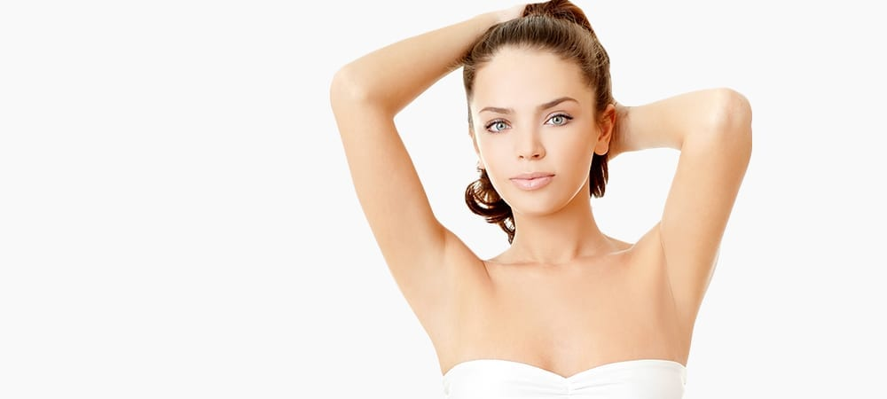 Brunette With Arms Behind Head Wearing Strapless Bra on White Background