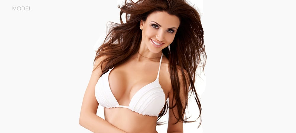 Female Model With White Bikini Top Smiling With Blown Back Hair
