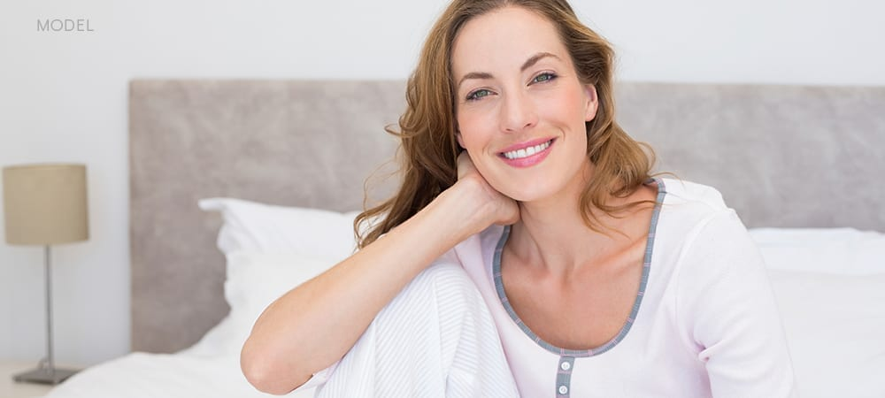 Caucasian Female In Pajamas Smiling While Sitting On Bed