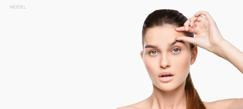 Brunette Pinching Area Between Hairline and Eyebrow With Surprised Look On Face