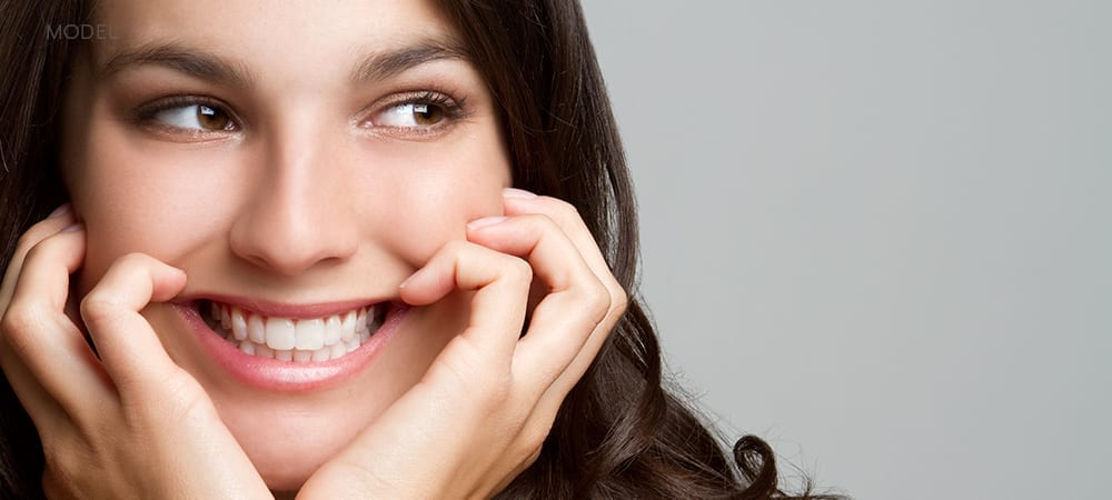 Close Up of Brunette's Face Smiling With Fingers Cupping Cheeks
