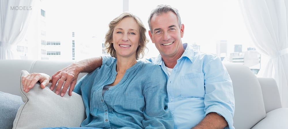 Mature Caucasian Couple In Blue Shirts Embracing on Gray Couch