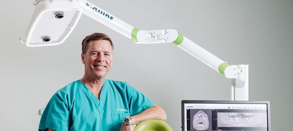 Dr. Emery Smiling In Front of X-Guide Machine