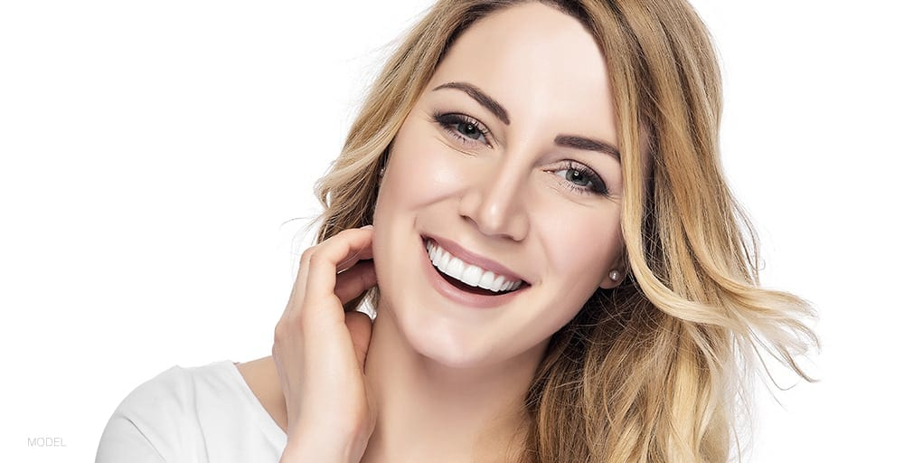 Caucasian Female Tilting Head Left Smiling With One Hand On Neck