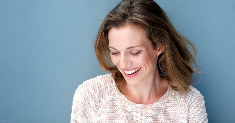 Brunette Model With Eyes Closed Wearing Sweater On Blue Background
