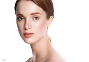 Female Model With Red Hair and Eyebrows Gazing at Camera In Bare Shoulders