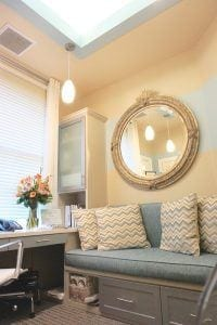 Office Desk Next To Teal Couch With Pillows and Large Mirror Above
