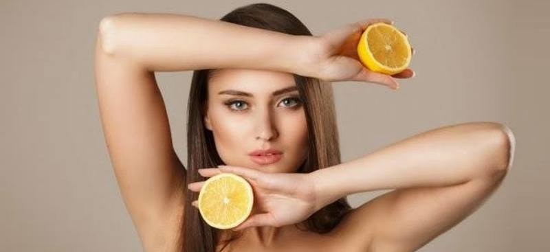 Model Holding A Slice of Lemon In Each Hand Framing Head With Arms