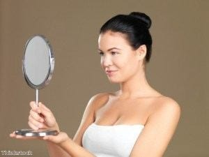 Female In White Strapless Shirt Looking at Herself In Handheld Magnifying Mirror