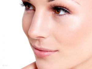 Close Up of Female's Face With Long Full Lashes, Brown Eyes, and Smooth Skin