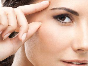 Close Up of Female Face Touching Index Finger and Thumb Around Eye Area
