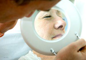 View of Mature Female Face Through Magnifying Glass Viewed by Doctor