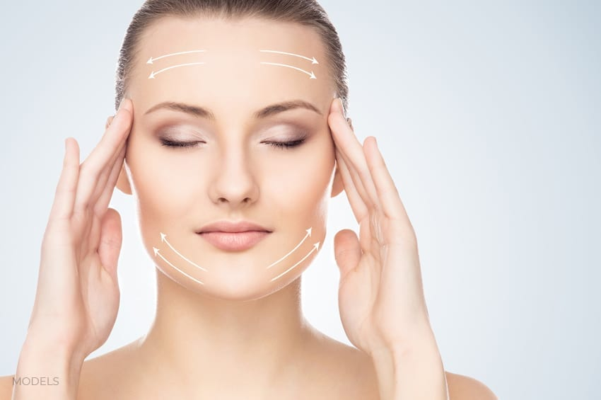 Female Model With Eyes Closed Touching Fingers to Temples With Arrows on Forehead and Chin Area