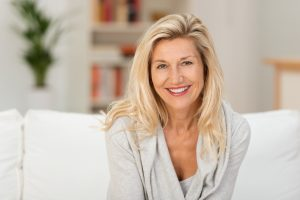 Middle Aged Blonde Woman Smiling On Sofa