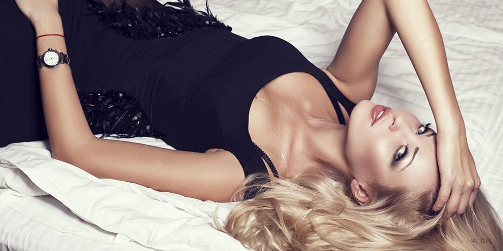 Elegant Blond Woman Laying Down on Bed