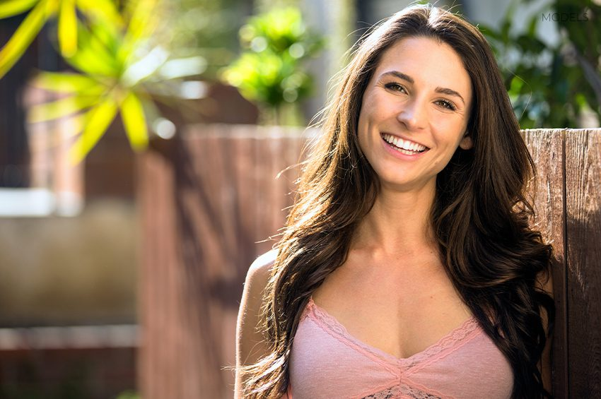 Adult Woman Smiling and Leaning on Yard Fence
