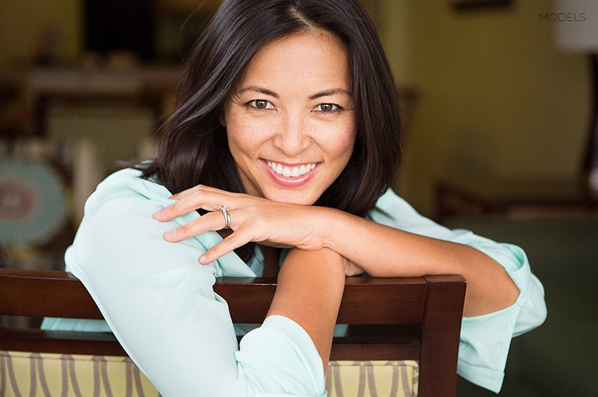 Middle Aged Woman Smiling and Leaning Over the Back of a Chair