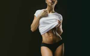 Mid-Body shot of Fit Woman in Black Underwear and a White Shirt