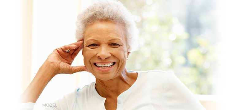 Older Female Patient Smiling and Showing Off Dental Implants