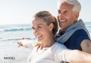Older Couple with Nice Teeth Holding Arms Out at Beach