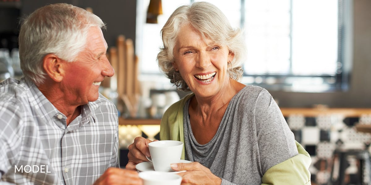 Mature Couple with Dental Implants Smiling and Holding Tea Cups