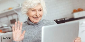 Smiling Mature Female Researching Questions About Dental Implants on Laptop