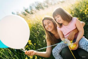 Girl with Special Needs Sister Holding Balloon and Smiling