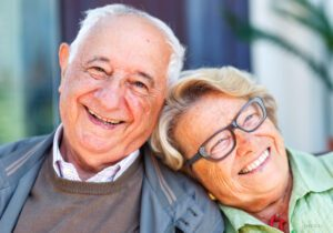 Older Couple Smiling Outdoors and Leaning on Each Other