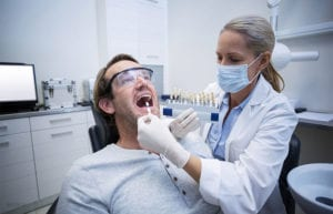 Female-dentist-examining-patient