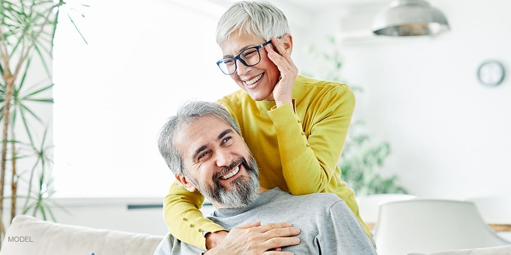 Older Couple with Dental Implants Smiling and Embracing