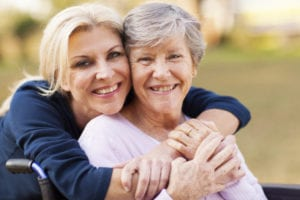 middle aged woman embracing disabled senior mother