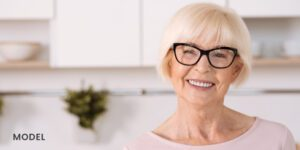 Older Female Patient Smiling with Dental Implants in Kitchen