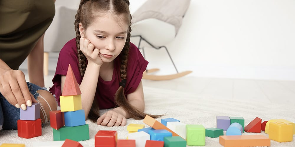 A female child playing with colorful blocks