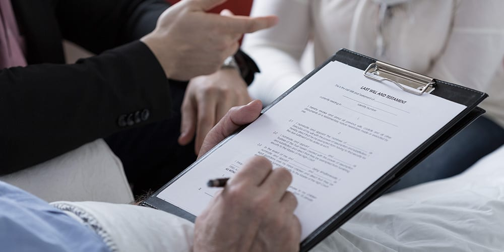 Man signing last will with lawyer