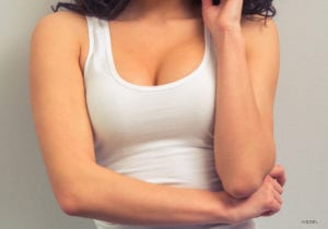 Female Torso Showing Lifted Breasts in White Tank