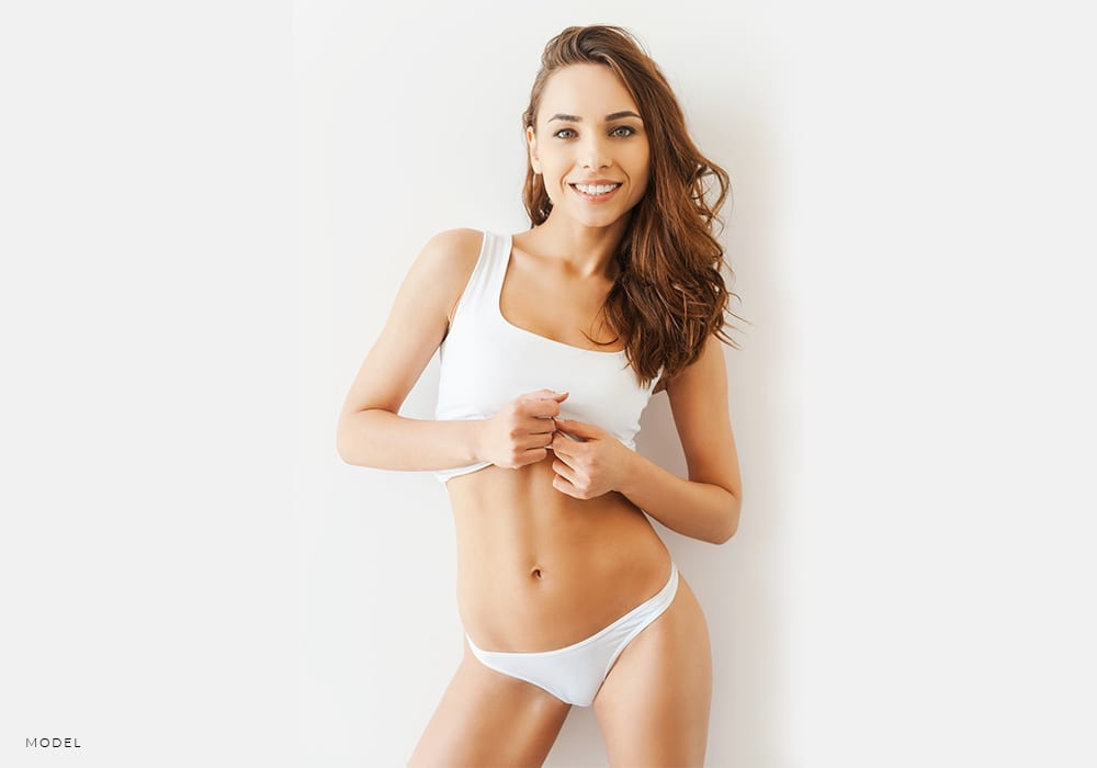 Female Model in Panties Lifting Up White Tank to Show Tummy