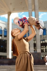 Mom in Brown Dress Lifting Baby Over Head