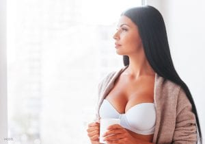 Sexy Model in White Bra and Open Sweater Holding Mug