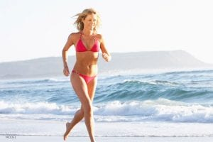 Female in red bikini running on beach