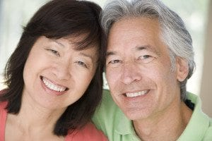 Couple with Dental Implants Smiling With Heads Touching