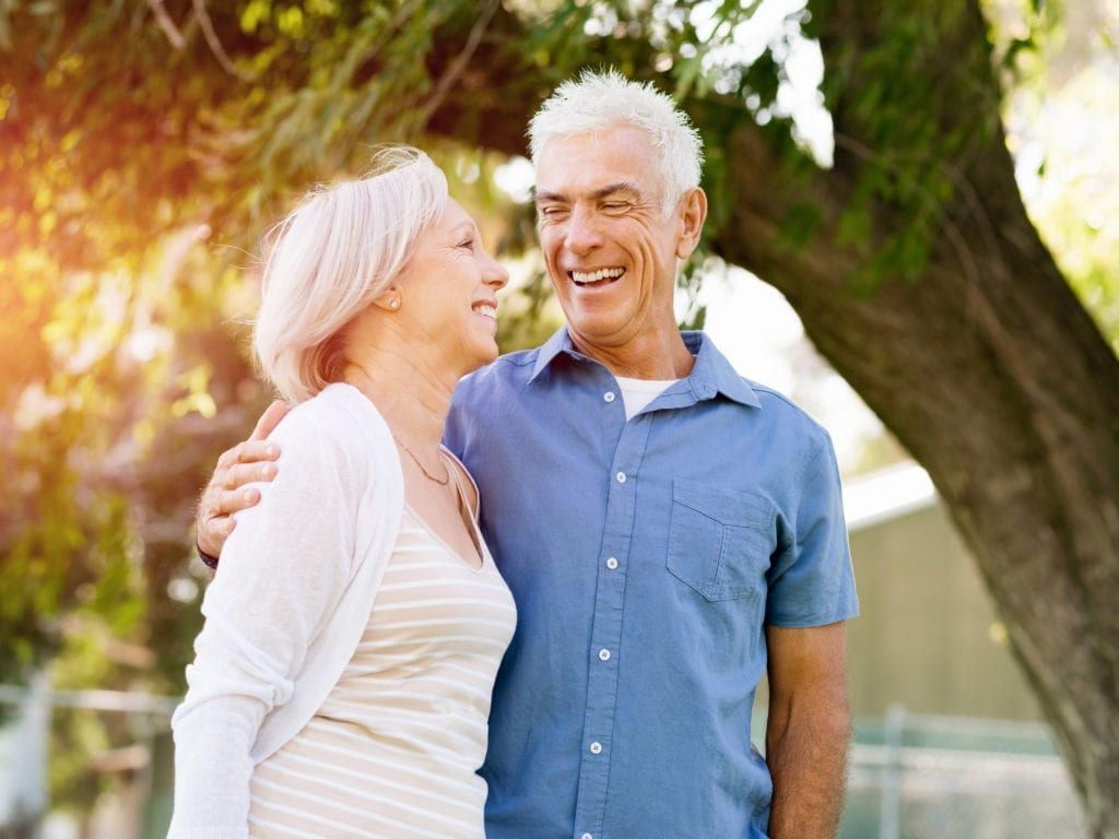 Older Couple Smiling In Front Of Trees With Sun Shining Through