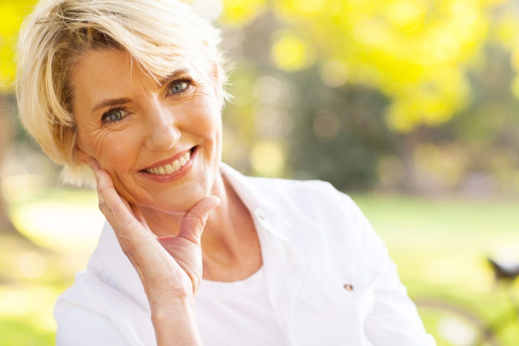 Older Woman Smiling Sitting Outside With Trees
