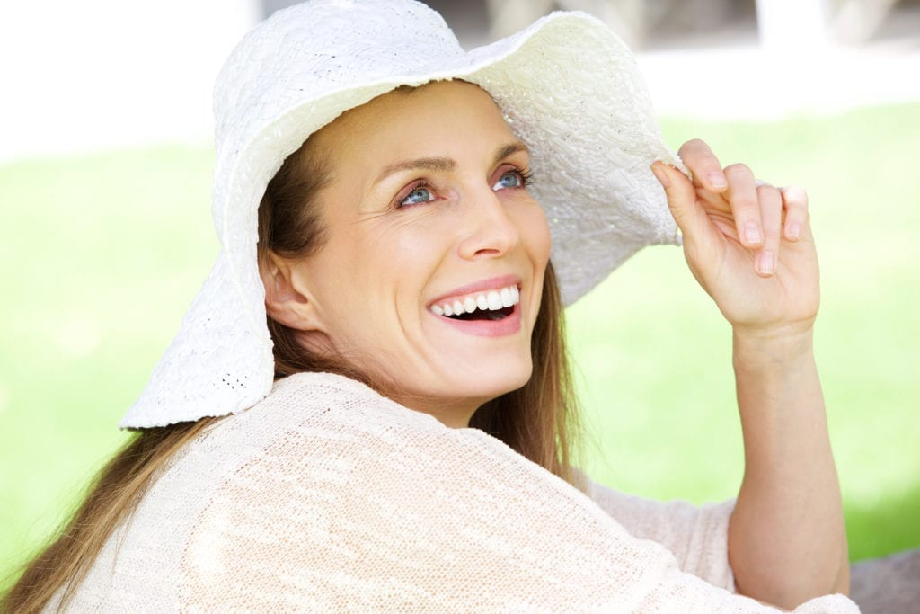Woman With White Hat Smiling Outdoors