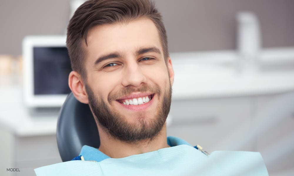 Young Male Smiling and Waiting for Wisdom Teeth Extraction in Dental Office Chair