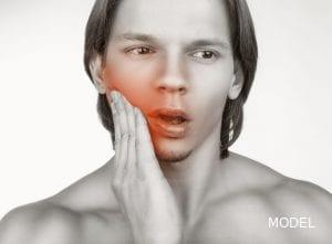 Young Male Holding Cheek in Pain