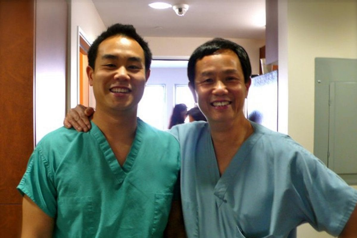 dr. Michael chan with his father in scrubs smiling