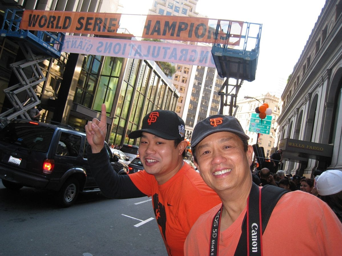 Dr. Chan with father pointing at a world series champions sign