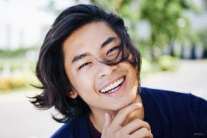 Smiling Young Man with long Hair Blowing in His Face