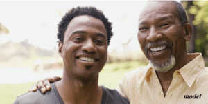 Smiling Young Man Standing Next to Smiling Father