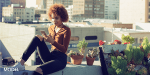 Young Woman Sitting on the Ledge Of A Building On Her Phone